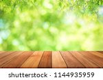 empty wooden table with garden... | Shutterstock . vector #1144935959