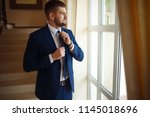 groom at wedding tuxedo smiling ... | Shutterstock . vector #1145018696