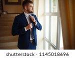groom at wedding tuxedo smiling ...   Shutterstock . vector #1145018696