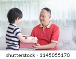 cute asian child giving a red... | Shutterstock . vector #1145055170
