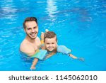 father teaching son to swim... | Shutterstock . vector #1145062010