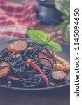black spaghetti with shrimps... | Shutterstock . vector #1145094650