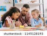 teacher in eyeglasses helping... | Shutterstock . vector #1145128193