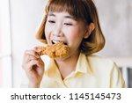 attractive asian woman eating... | Shutterstock . vector #1145145473