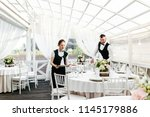 two waiters serve at the... | Shutterstock . vector #1145179886