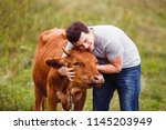 young man hugging cow | Shutterstock . vector #1145203949