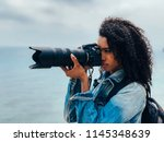 woman taking a picture of a sea ... | Shutterstock . vector #1145348639