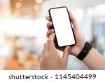 man using smartphone at... | Shutterstock . vector #1145404499