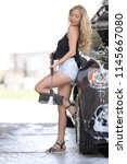 a blonde woman washing a suv car | Shutterstock . vector #1145667080