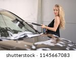 a blonde woman washing a suv car | Shutterstock . vector #1145667083