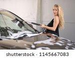 a blonde woman washing a suv car | Shutterstock . vector #1145667083