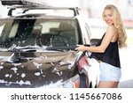 a blonde woman washing a suv car | Shutterstock . vector #1145667086