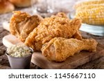 Small photo of Delicious crispy fried chicken with coleslaw and corn on the cob.