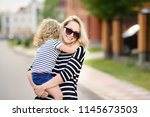 young mother holding her little ... | Shutterstock . vector #1145673503