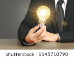 hand holding a light bulb with... | Shutterstock . vector #1145710790