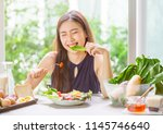 young asian woman happy eating... | Shutterstock . vector #1145746640