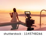 Video camera filming actress woman acting for movie on luxury hotel location behind the scenes of shoot. Professional videography equipment shooting outdoor at sunset. - stock photo