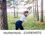 woman doing exercises in a park | Shutterstock . vector #1145854070