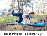 woman doing exercises in a park | Shutterstock . vector #1145854169