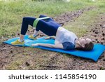 woman doing exercises in a park | Shutterstock . vector #1145854190