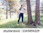 woman doing exercises in a park | Shutterstock . vector #1145854229