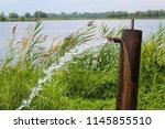 wellspring next to a lake | Shutterstock . vector #1145855510