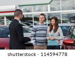 Small photo of Salesman talking to a couple in a dealership