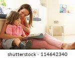 mother sitting with son reading ... | Shutterstock . vector #114642340