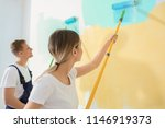 Young painters using rollers for refurbishing color of wall indoors - stock photo