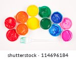 motley paints on the white background. paints arranged as rainbow with plastic fork partly colored in green paint. studio shot - stock photo