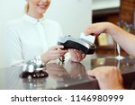 guest at hotel reception paying ... | Shutterstock . vector #1146980999