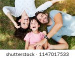 family smiling together in park | Shutterstock . vector #1147017533