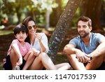 happy family sitting in park ... | Shutterstock . vector #1147017539