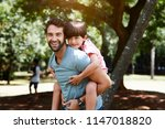 dad carrying boy on back in... | Shutterstock . vector #1147018820