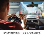 man driving car while eating... | Shutterstock . vector #1147052096