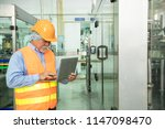 senior engineer inspecting... | Shutterstock . vector #1147098470