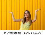 pretty young woman holding...   Shutterstock . vector #1147141103