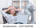 woman suffers from heat while... | Shutterstock . vector #1147165940
