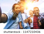 young family taking a selfie... | Shutterstock . vector #1147210436