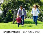happy family running at the park | Shutterstock . vector #1147212440