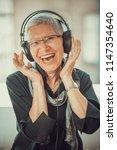 senior old woman listening to... | Shutterstock . vector #1147354640