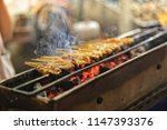 pork satay grilling on stove or ... | Shutterstock . vector #1147393376