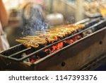 pork satay grilling on stove or ... | Shutterstock . vector #1147393376