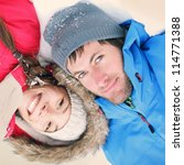 Winter couple happy. Overhead view of the heads of happy attractive interracial Asian / Caucasian couple lying in snow in warm winter clothing - stock photo