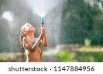 cute little girl pours herself... | Shutterstock . vector #1147884956