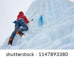 alpinist woman with  ice tools... | Shutterstock . vector #1147893380