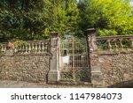 rusty gate in an old wall in... | Shutterstock . vector #1147984073