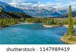 Saskatchewan River - A Spring evening view of colorful Saskatchewan River calmly flowing below rugged ridge of Mount Hensley, Banff National Park, AB, Canada.