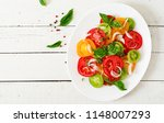 colored tomato salad with onion ... | Shutterstock . vector #1148007293