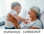 grandmother and baby boy having ... | Shutterstock . vector #1148063429